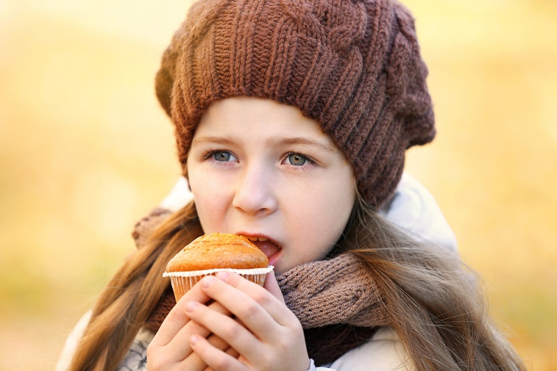 Cute little girl eating tasty muffin outdoors, close up view